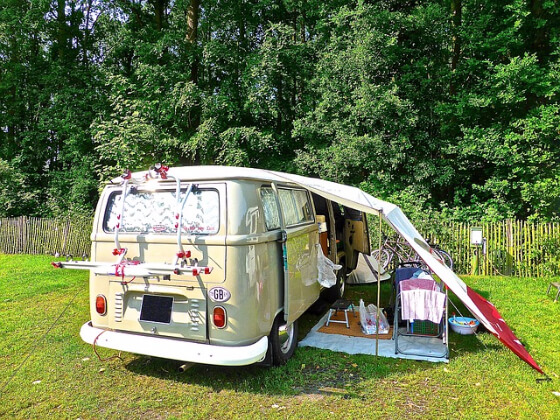 Van is camped with folding chairs and a tarp awning making everything comfortable.