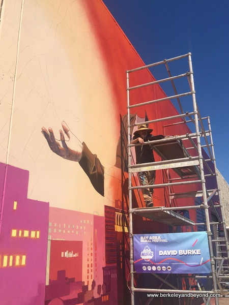 David Burke works on his mural at Jack London Square in Oakland, California