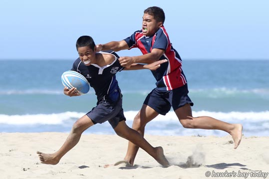 L-R: Junior Telea, Napier Intermediate School, Napier, running in for the last try of the game; Grayson Hesketh, Hastings Intermediate School, Hastings -  0800 Beach 5's, a three-day beach rugby competition  at Ocean Beach, 16 different teams each day, from intermediate and full primary schools from Hawke's Bay. photograph