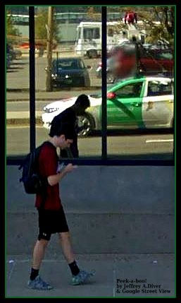Young man in red shirt with backpack texts, oblivious to his shadow on the nearby window and the Google Street View vehicle passing by