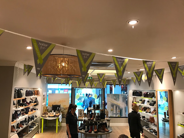 A photo of the shoe shop with bunting on the ceiling