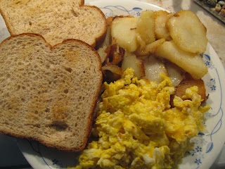 breakfast plate of eggs, toast, and leftover fried potatoes