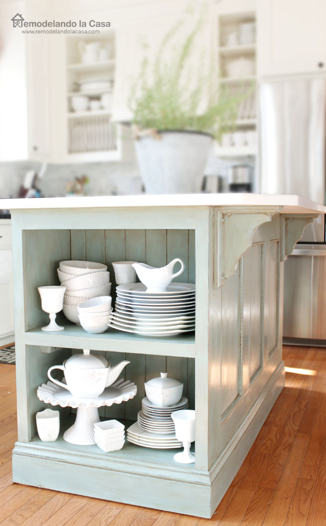 kitchen island with shelf on one end, beadboard, white dishes and white counter