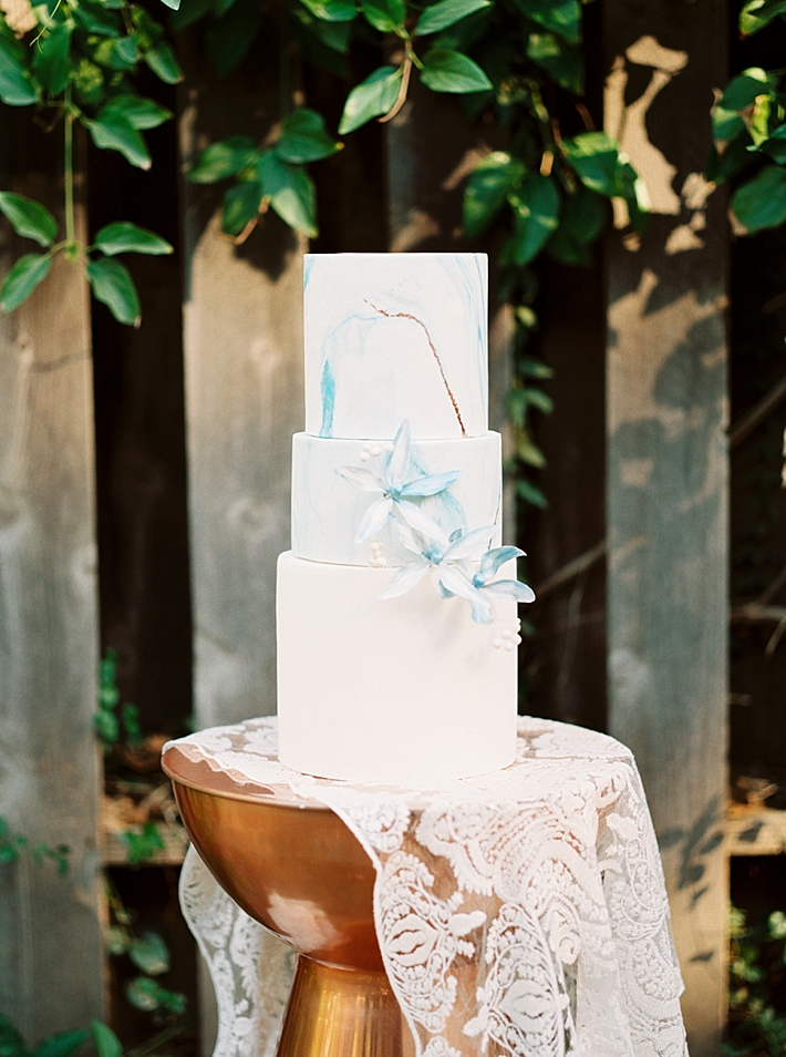 White and blue marble wedding cake with floral details | Photo by Dennis Roy Coronel | See more on thesocalbride.com