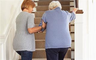 hija ayudando madre anciana a subir escaleras