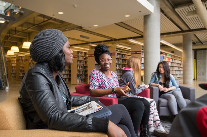 students discussing in comfortable chairs in the library