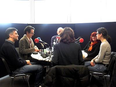 Im Gegenlicht: Menschen sitzen um einen runden Tisch herum, auf dem Mikrofone stehen
