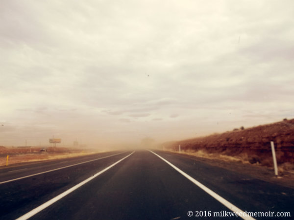 Wind-blown dust and cloud cover obscures I-40 straight ahead near Winslow, Arizona.