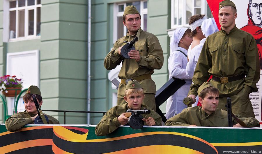 Парни в военной форме времён войны и автоматами ППШ. Театрализованный парад 'Все мы - Россия!'