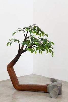 Escultura de martillo en un extremo y árbol en el otro.