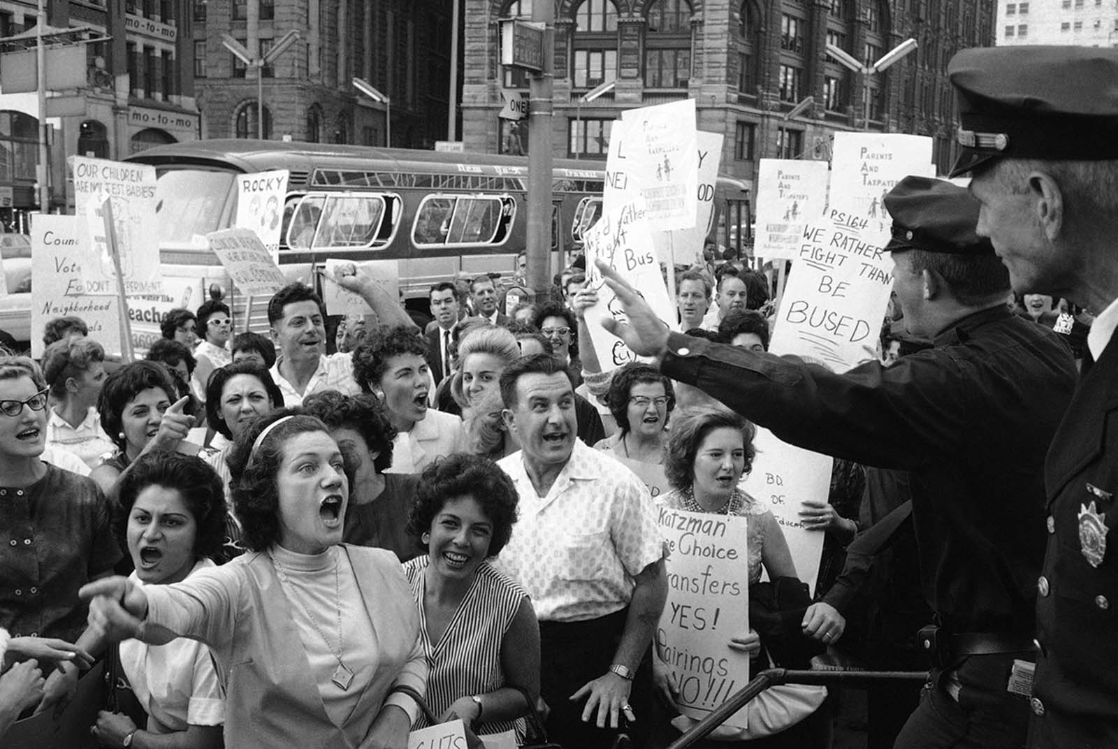Demonstrators shout at policemen who ask them to move on along City Hall in New York, Sept. 24, 1964 as they protest a Board of Education busing program aimed at increasing racial balance in New York City schools.