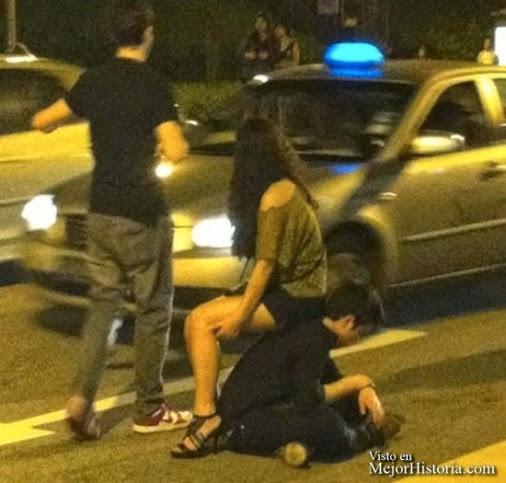 Chico sentado en la acera ofrece su espalda a chica como asiento mientras esperan un taxi.