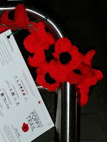 A string of poppies attached to a chrome bannister. A laminated tri-panel leaflet is attached to the poppies.