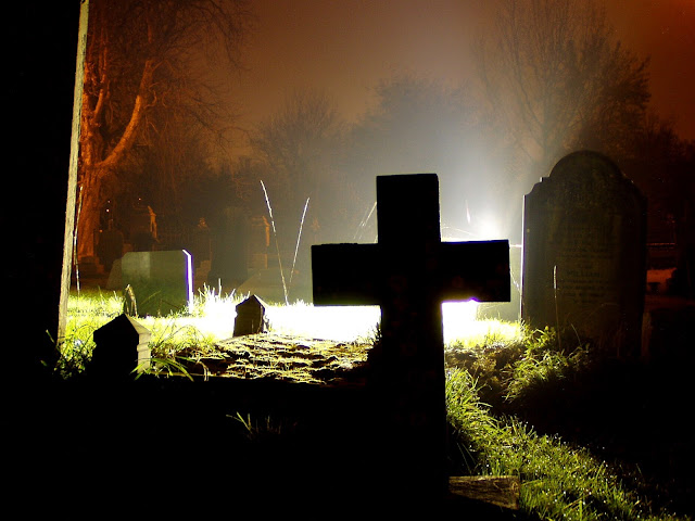 A Northampton churchyard photographed at night highlighting the various headstones