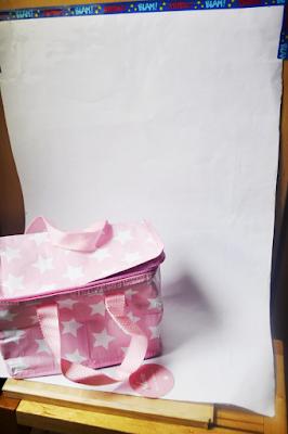 la bolsa sobre una cartulina blanca pegada con celo a una pared y a una silla