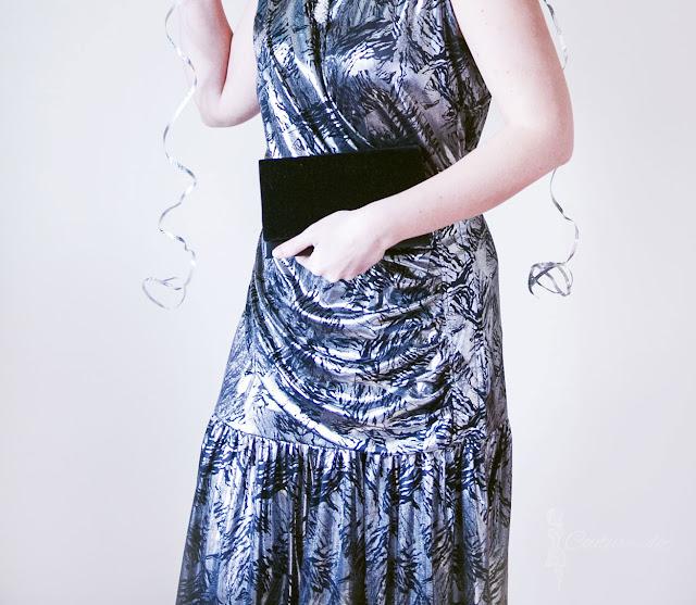 srebrna sukienka z czarnym motywem, czarna aksamitna torebka