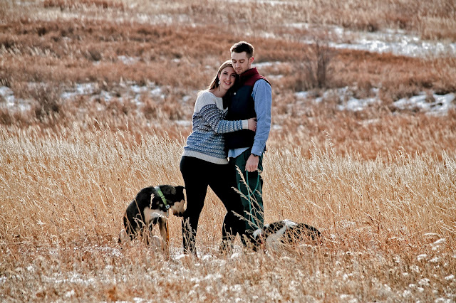 a woman leans her head into her fiances chest as they pose for an engagement session with their dogs in Boulder Coloraod