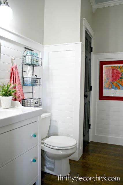 White bathroom with wood floors and black door