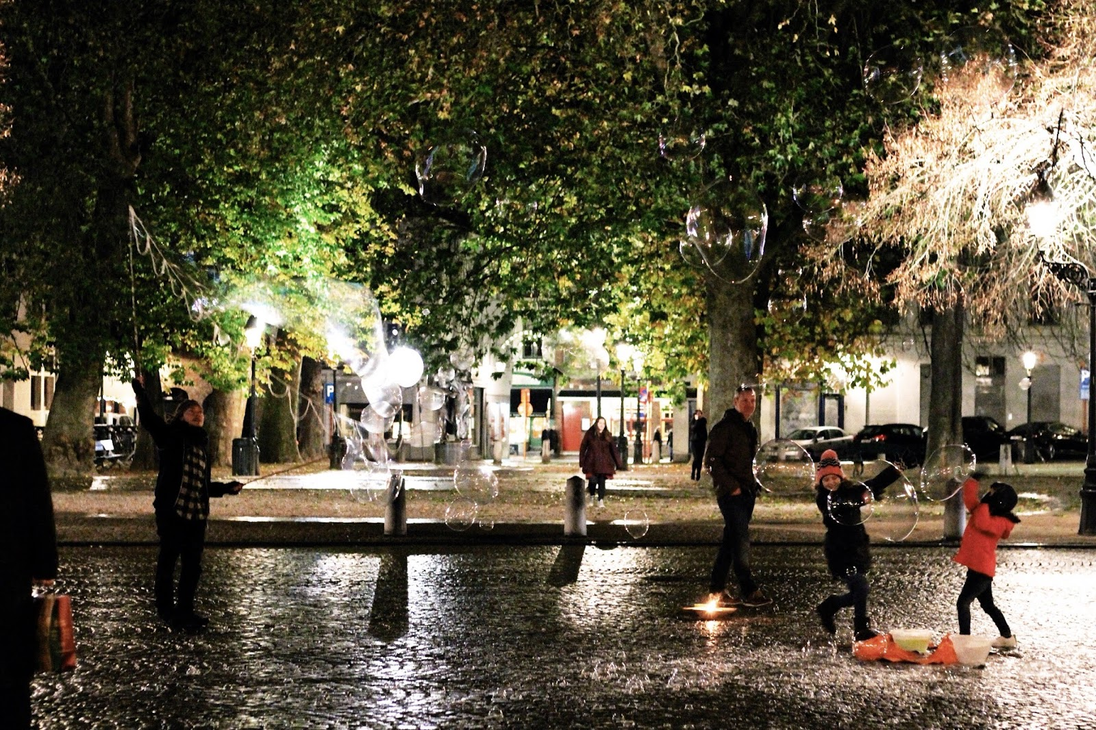 Children playing with bubbles on a rainy night in Bruges