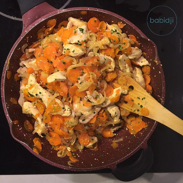 vue de dessus d'une sauteuse remplie de poulet sauté au sésame et aux carottes oignons ciboulette sauce soja posée sur une plaque de cuisson