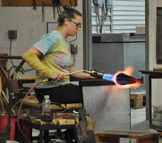 woman using blowtorch to help shape glass vase