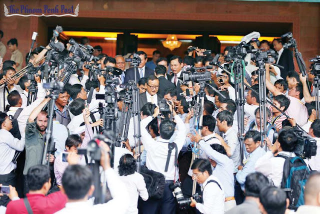 Members of the press gather at the entrance to the Senate in Phnom Penh as politicians depart after a political meeting in 2014. Heng Chivoan