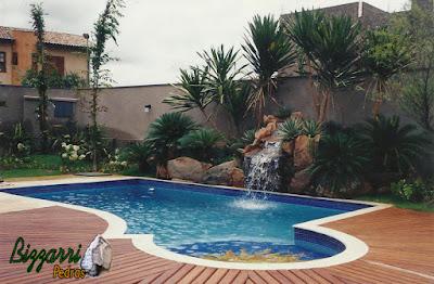 Cascata de pedra na piscina, tipo pedra moledo, com execução do paisagismo e piscina com o deck de madeira.