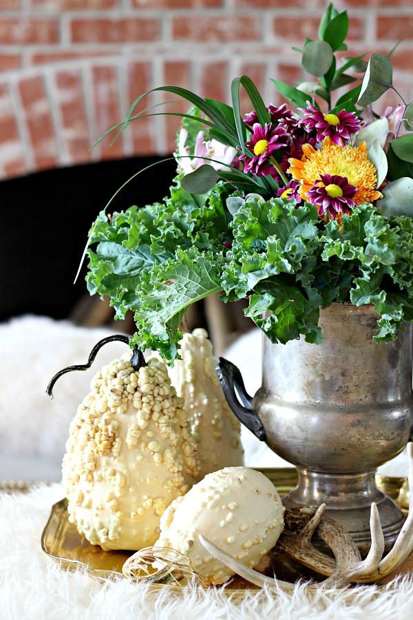 fresh flowers, kale, white pumpkins, faux fur, brick fireplace, antlers, brass tray, vintage silver urn