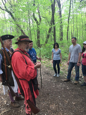 Visitors exploring woods at Bushy Run during spring nature walk