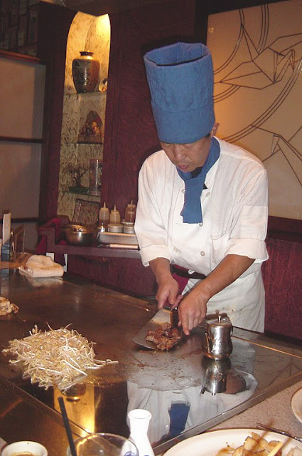 Photo of an Asian cook making a steak dinner on a large griddle.