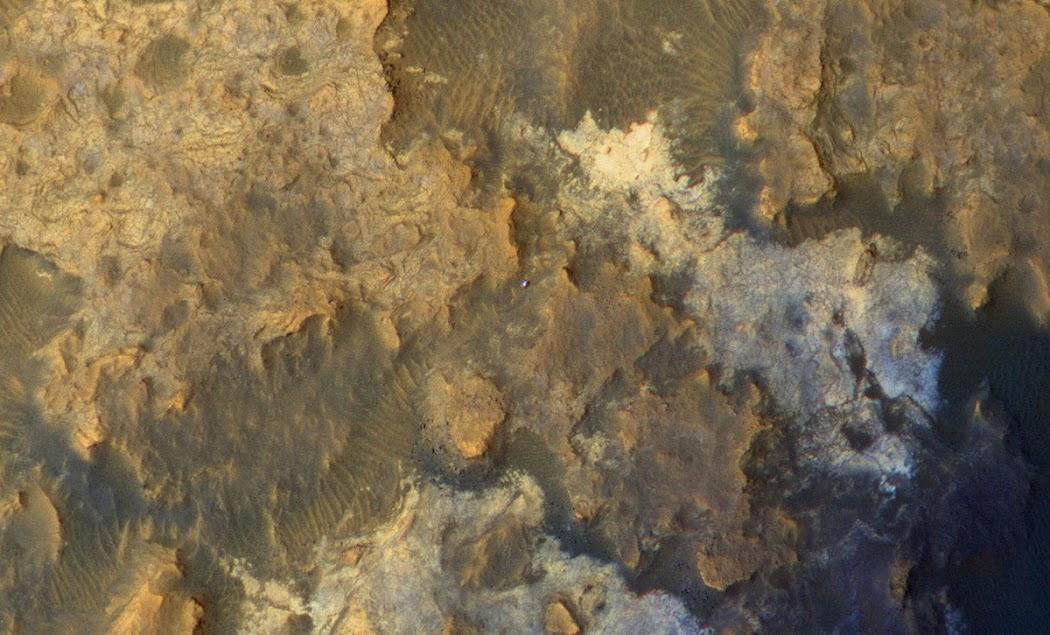 Đây là hình ảnh được chụp từ trên cao. Được thực hiện vào ngày 8 tháng 4 năm 2015 bởi Tàu Thăm dò Quỹ đạo Sao Hỏa (Mars Reconnaissance Orbiter, hay MRO) của NASA, trong ảnh bạn có thể bắt gặp tàu Curiosity đang đi qua một thung lũng được gọi là Artist's Drive ở vùng chân núi Sharp. Đây là sol thứ 949 của Curiosity và nó đã đi được 23 mét trong ngày này. Hướng bắc địa lý nằm ở phía cạnh trên của ảnh, bóng của tàu đổ về hướng đông. Hình ảnh: JPL-Caltech/Univ. of Arizona/NASA.