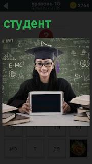 Девушка на фоне доски с формулами и головным убором студента на голове и с планшетом в руках