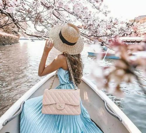 Uma jovem com vestes finas chapéu na cabeça, sentada em um barco com olhar perdido no tempo.