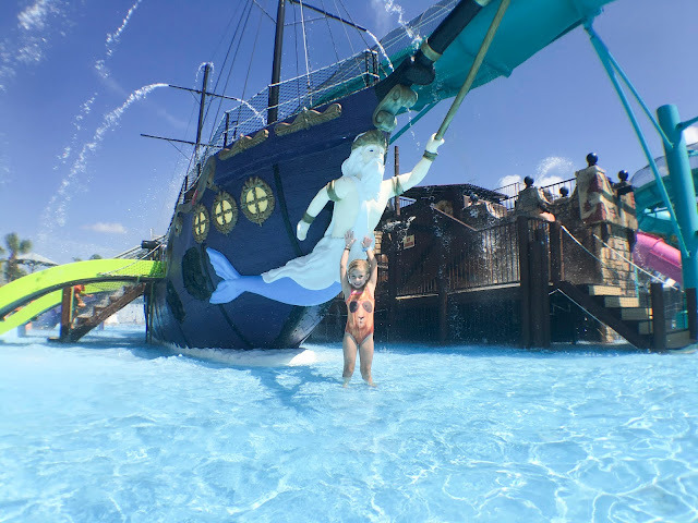 Little girl standing in front of color ship in waterpark