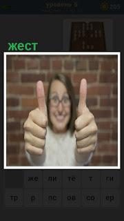 Женщина обеими руками показывает жест, два пальца вверх