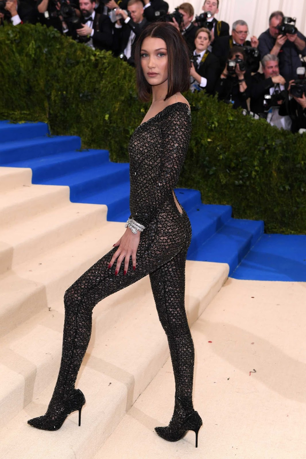 Bella Hadid perfectly showcased her flawless figure in a backless glittery catsuit by Alexander Wang as she arrived for the Met Gala on Monday night in New York City