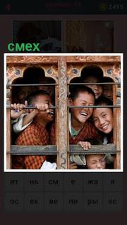 дети смотрят в окно на улицу и смеются