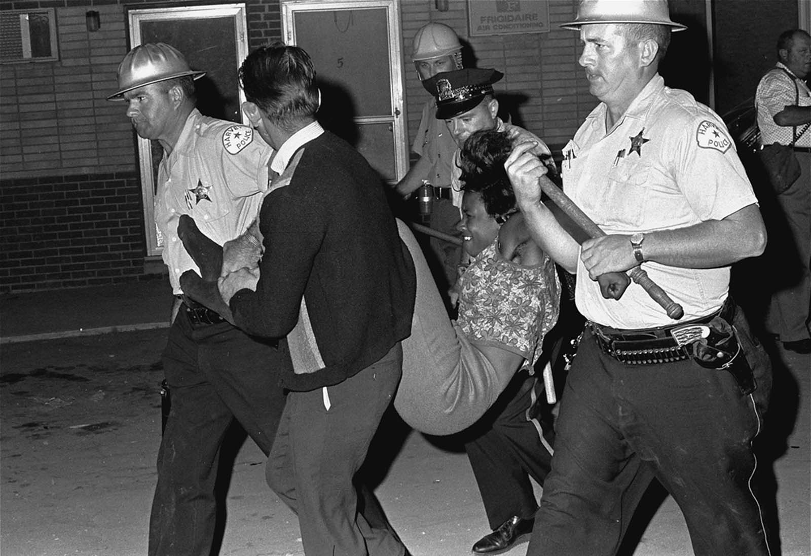 A woman who stayed at the riot scene in Dixmoor, IL, August 17, 1964, is carried to a police van. Police had ordered all persons indoors in the race riot area. Those who didn't, were taken into custody in Dixmoor, a Chicago suburb. More than twelve were arrested. A number of large cities across the eastern U.S. experienced race-related riots during the summer of 1964.