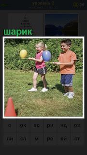 мальчик и девочка на палках впереди себя несут шарики