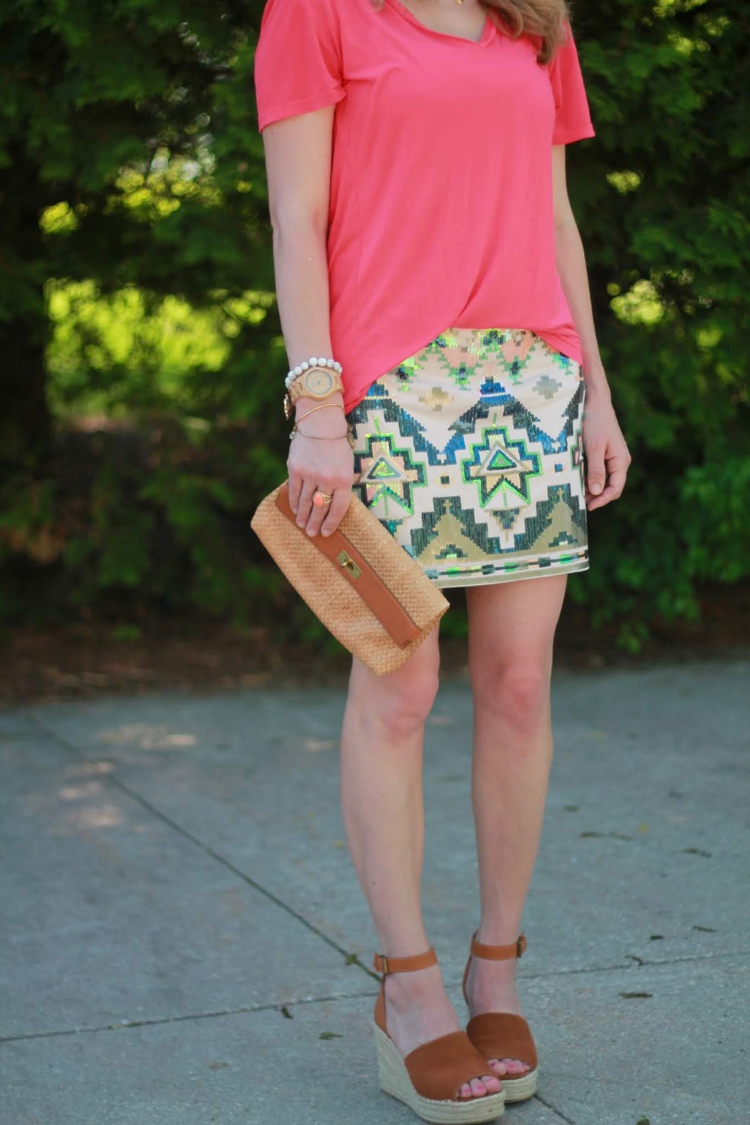 express sequin skirt, coral piko tee, cognac wedges, straw clutch
