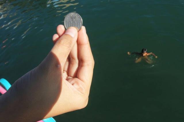 Seorang wisatawan bersiap melemparkan uang logam kepada seorang anak yang berenang di kawasan Pelabuhan Ajibata, Danau Toba, Toba Samosir, Sumut.