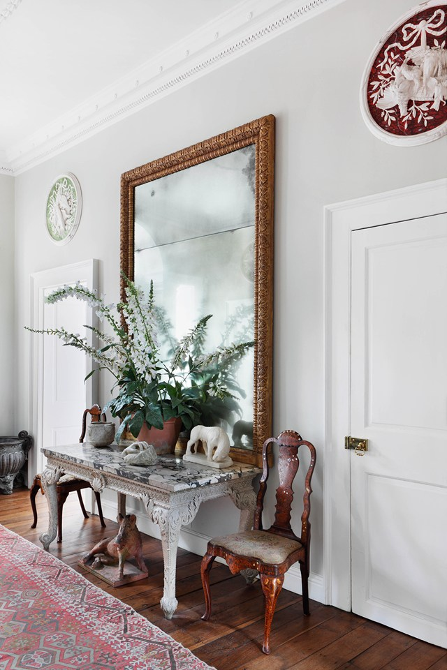 An eighteenth-century mirror hangs above a marble-topped table in the hall