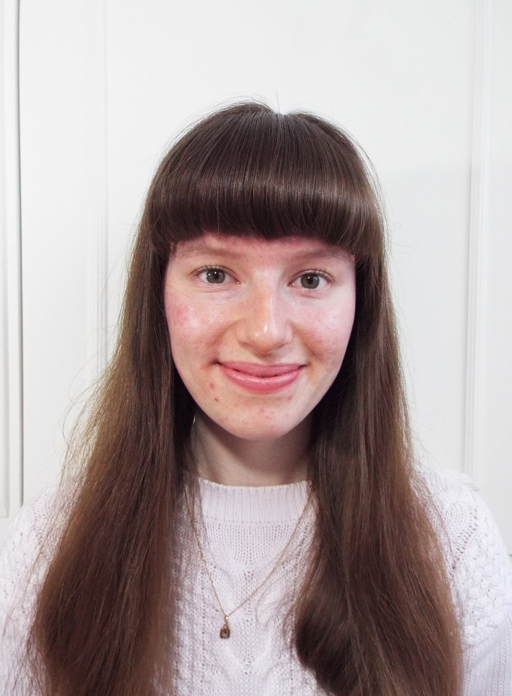 Ellie - blogger of Ellie Bows & Sparkles - with no makeup, full fringe and brown hair, curled lashes and pink lips, wearing a lilac jumper and her Nan's little gold necklace