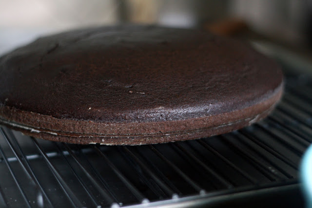 A baked chocolate cake with slight domed top resting on a wire rack.