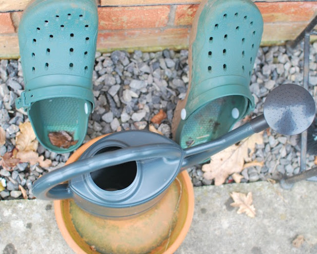 A pair of plastic green clogs, a watering can and a pot saucer.
