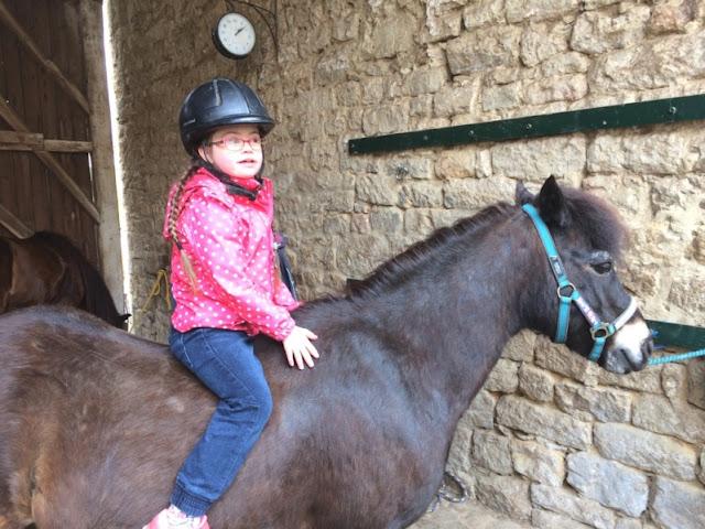 Jolina, Down Syndrom, auf einem Pony