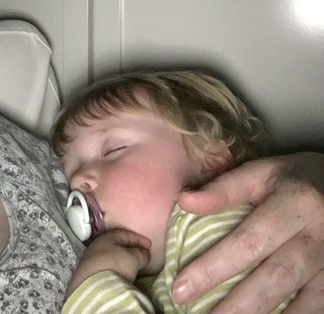 toddler-fast-asleep-in-the-arms-of-his-nanny
