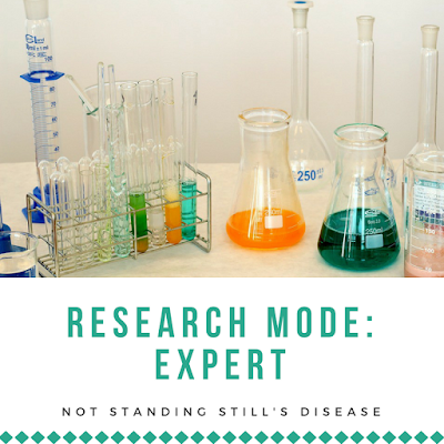 """photo of a lab setup with beakers and test tubes filled with various colored liquids; under this is a white background with green text """"Research Mode: Expert"""" under which is black text """"Not Standing Still's Disease"""" and under that is a line of diamonds in the same green color as the other text"""