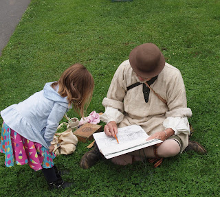 Costumed interpreter shows drawing of homestead to child