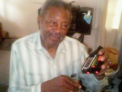 Willie showing me a case of harmonicas with a red  tuning letter on the bottom of each harmonica's box.